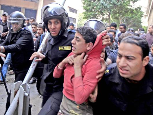 A child is detained by police during the recent clashes