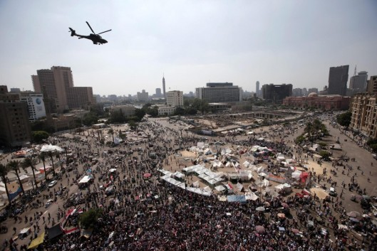 An Apache helicopter swoops over Tahrir Square